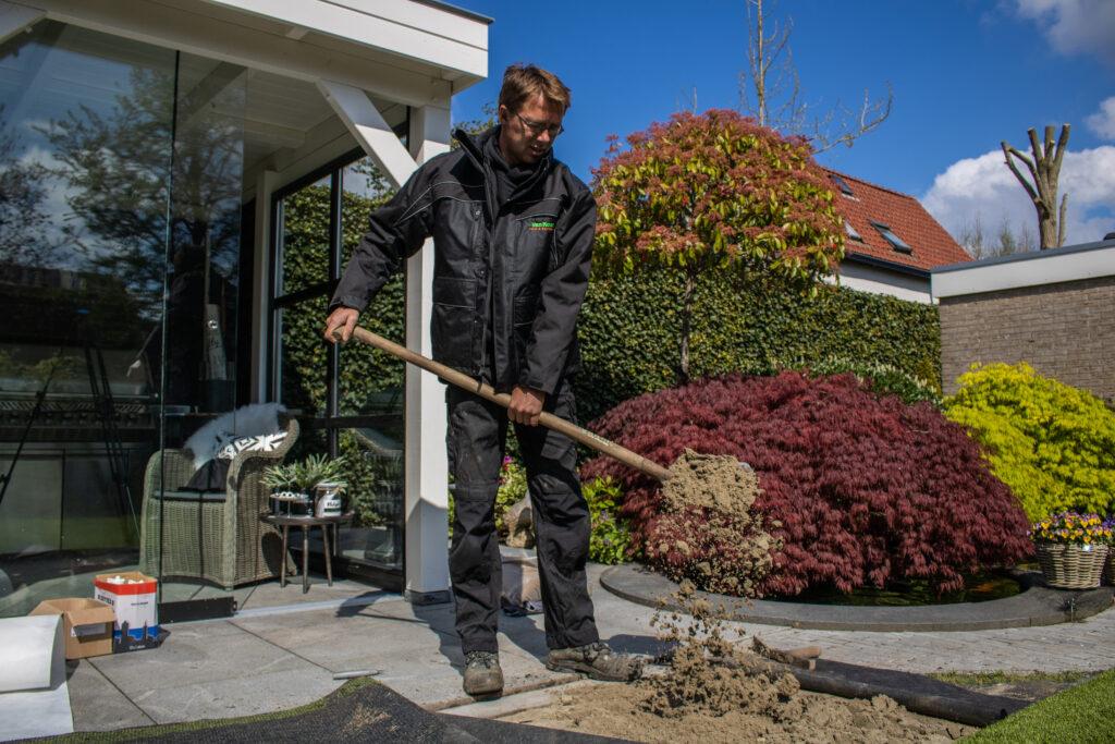 Het aanbrengen van een zandbed om het kunstgras uiteindelijk op aan te brengen.