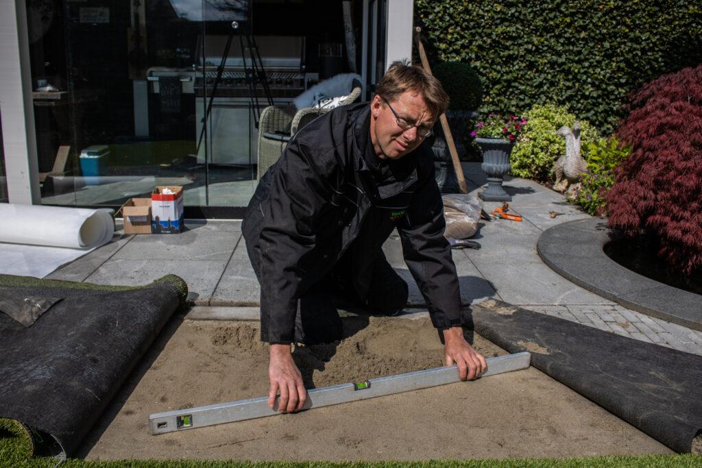 Het egaliseren van de onderlaag van zand met een waterpas.